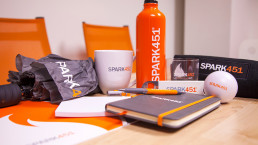 Photo of Spark451 branded mug, notebook, bottles, and more